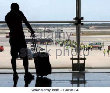 A passenger looks to the runway as the ground crew of Iberia take part in a protest to block airplanes from taking - Stock Photo