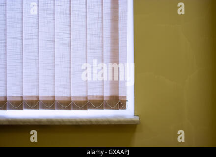 Fragment of window with jalousie closed on cracked old yellow wall. - Stock Photo