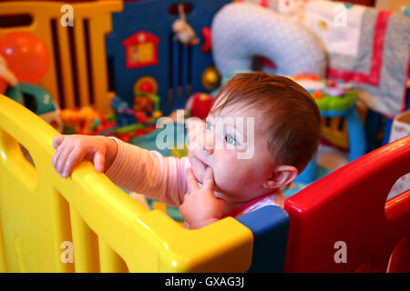 Baby girl thinking in a colourful playpen - Stock Photo