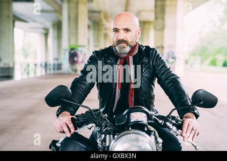 Portrait of mature male motorcyclist sitting on motorcycle under flyover - Stock Photo