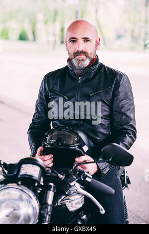 Portrait of mature male motorcyclist sitting on motorcycle - Stock Photo
