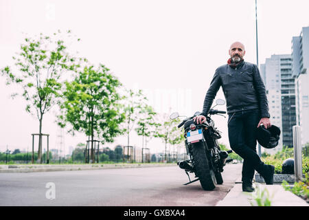 Portrait of mature male motorcyclist leaning on motorcycle - Stock Photo