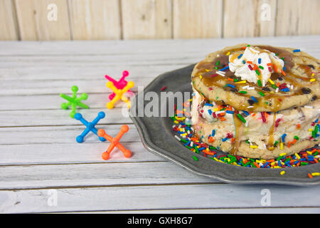 Cookie ice cream sandwich with caramel sauce and toy jacks on wood - Stock Photo