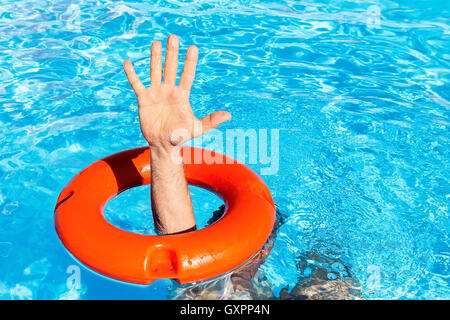 Arm with hand through orange buoy in blue swimming pool - Stock Photo