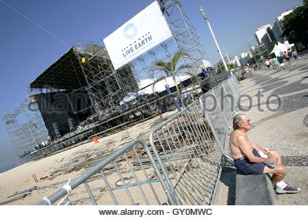 A man sits near the site for the Live Earth concert as workers set up the stage on Copacabana Beach in Rio de Janeiro - Stock Photo