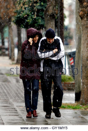A couple walk by a public park under a surprise snowfall in Buenos Aires July 9, 2007. The last time it snowed in - Stock Photo