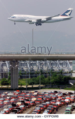 A landing Cathay Pacific Airways Boeing 747 passenger plane flies past columns of taxis at the Hong Kong airport - Stock Photo