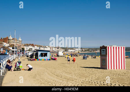 People on sandy beach in late summer September sunshine. Melcombe Regis, Weymouth, Dorset, southern England, UK, - Stock Photo