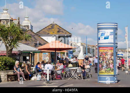People dining in sunshine outside a pavement cafe ice cream parlour on Weymouth seafront promenade. Melcombe Regis - Stock Photo