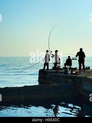 Group of fishers on a pier at sunset. Crimea peninsula - Stockfoto
