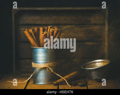 Cinnamon sticks in metal jar on wooden table, rustic tray at background, selective focus, copy space - Stock Photo