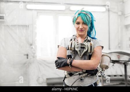 portrait young woman paint gun auto body shop - Stock Photo