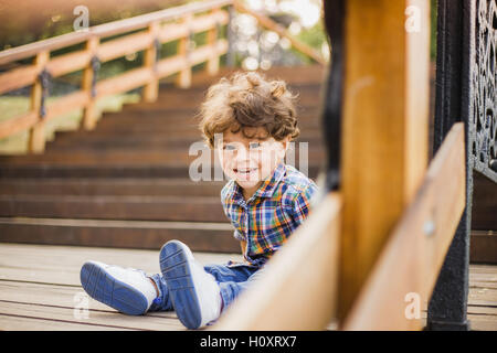 Portrait of little cute child sitting on wood stairs in city park. Boy looks at camera through wooden parapet of - Stock Photo