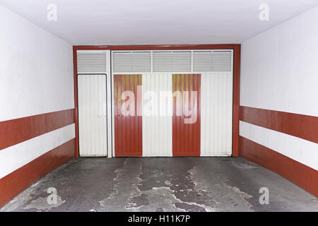 Red and white door in garage townhouse, construction - Stock Photo