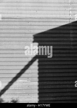Black and white image outback Australia. Shadow of water tank on corrugated iron wall. - Stock Photo
