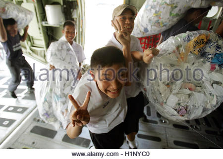 Thai school children help to load the tens of millions of paper birds into planes in Bangkok December 3, 2004. Bags - Stock Photo