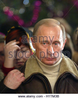 Russian President Vladimir Putin crosses himself at a Christmas service in the ancient Church of Nativity of the - Stock Photo