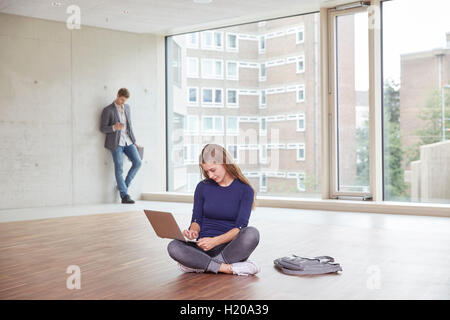 Young woman using laptop in empty room with man in background - Stock Photo