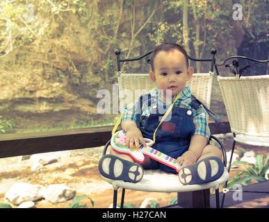 Asian baby boy who wear dungarees is sitting on the chair in his hand holding guitar toy beside the creek in the - Stock Photo