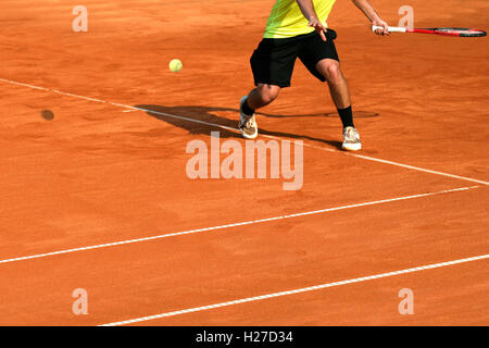 Male tennis player in action on the court on a sunny day - Stock Photo