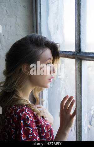 Profile of a serious woman looking out of the window - Stockfoto