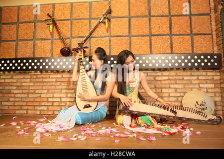 Vinh Long, Vietnam - November 4, 2015: Two young girls are playing Vietnamese traditional instruments in a restaurant - Stock Photo