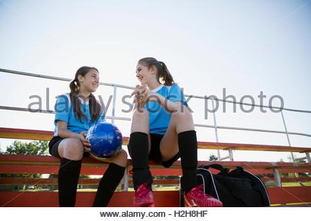 middle school girl soccer teammates talking on bleachers - Stockfoto