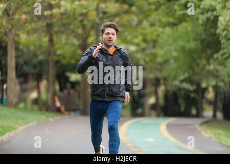 Athletic man running in a rainy day. - Stock Photo