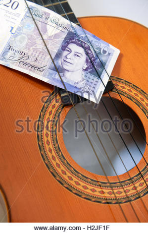 Acoustic guitar and 20 pound note. Notes on notes. - Stock Photo