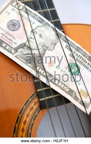 Acoustic guitar and 10 dollar note. Notes on notes. - Stock Photo