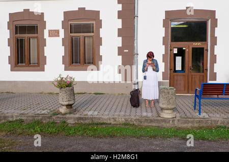 Pretty woman checking message on her cell phone at the train station in Zarnovica, Slovakia - Stock Photo