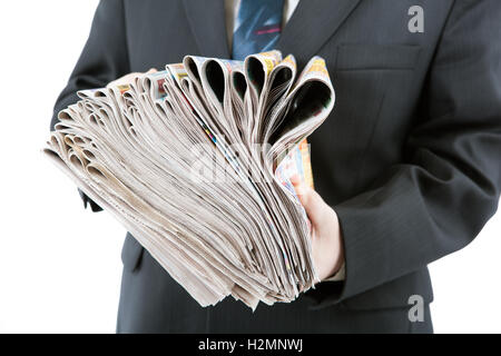 man's hands holding a stack of newspapers - Stock Photo
