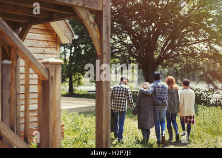 Friends walking outside lakeside cabin - Stock Photo