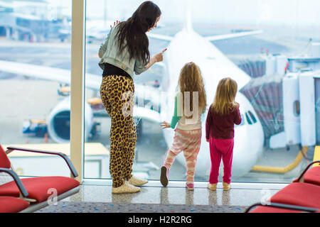 Little cute girls and young mother near large window in airport looking at the plane - Stock Photo