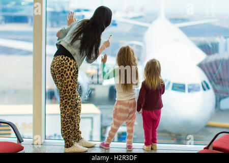 Little cute girls with mom near large window in airport looking at big aircraft - Stock Photo
