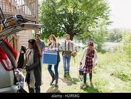 Friends loading cooler and belongings into car outside sunny cabin - Stock Photo