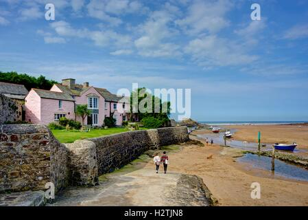 A fresh seaside landscape of  two people holding hands walking down to Bude harbour in Cornwall on a lovely late - Stock Photo