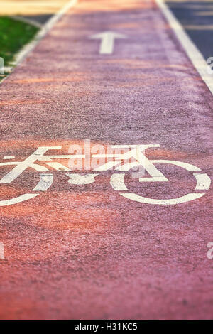Red bike lane on sidewalk with painted white bicycle and arrow signs. Copy space - Stockfoto