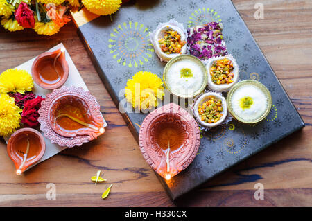 diya lamps lit during diwali celebration with flowers and sweets in background - Stock Photo