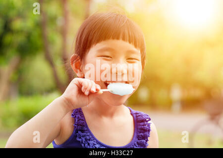 happy little girl eating popsicle with sunset background - Stock Photo