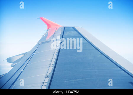 Wing aircraft in blue sky captured from window - Stock Photo