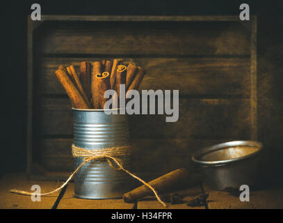 Cinnamon sticks in tin can, rustic wooden background, copy space - Stock Photo