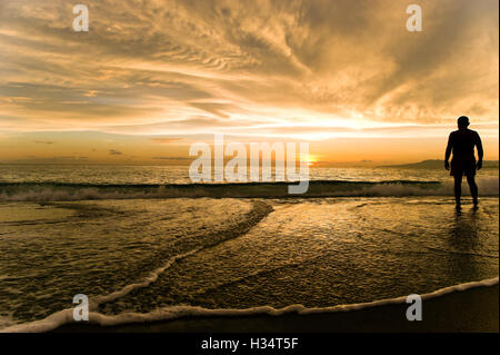 Sunset man is a silhouette of a man standing in ocean water looking at the sunset with awe. - Stock Photo