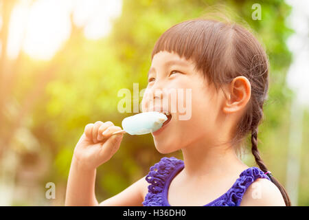 happy little girl eating popsicle at summertime with sunset - Stock Photo