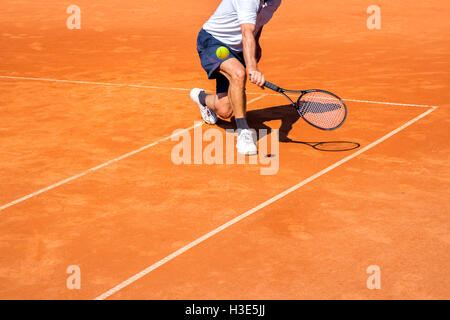 Male tennis player in action on the clay court on a sunny day - Stock Photo