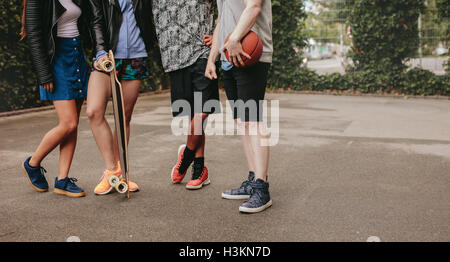 Cropped shot of group of people standing together with basketball and skateboard. Low angle shot with focus on men - Stock Photo