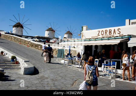 Windmills and tourists on Mykonos, Greece - Stock Photo