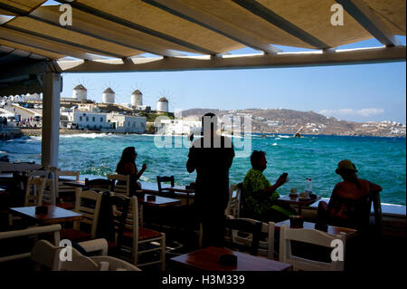 View of windmills from seaside cafe in Mykonos, Greece - Stock Photo