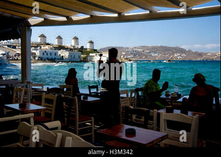 View of windmills from seaside cafe in Mykonos - Stock Photo