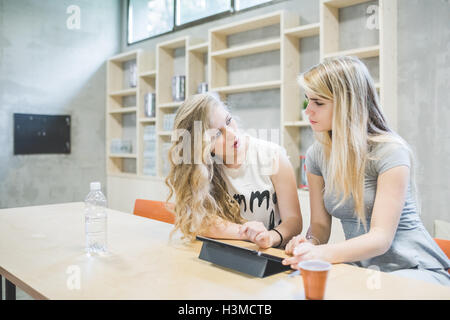 Co-workers working on digital tablet in office - Stock Photo